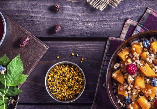 Healthy breakfast with pumpkin porridge, berries and herbal tea with honey at village summer house