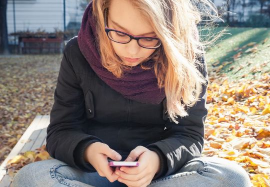 Cute Caucasian blond teenage girl in jeans and black jacket sitting on park bench and using smartphone, outdoor autumn portrait