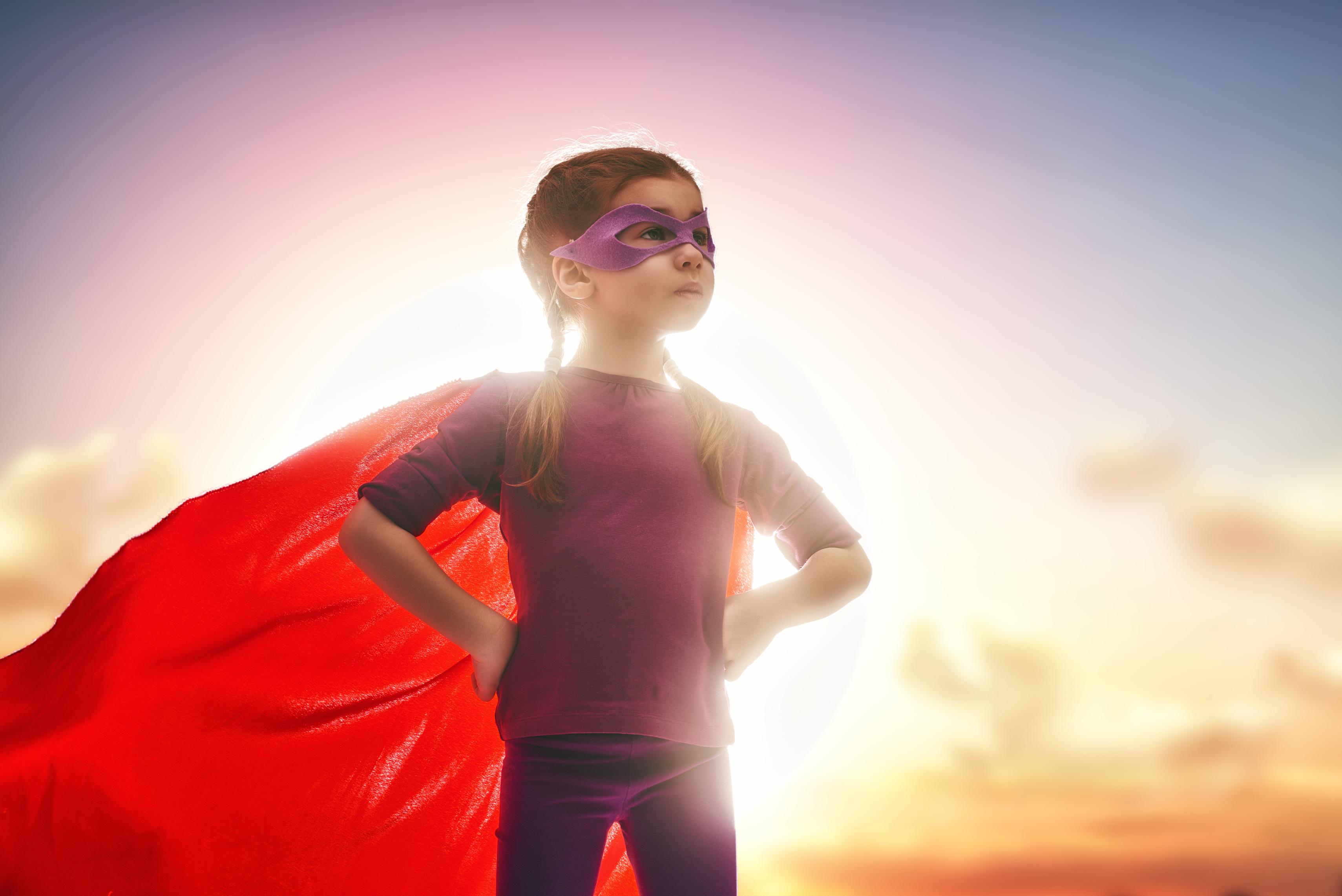 Little child girl plays superhero. Child on the background of sunset sky. Girl power concept