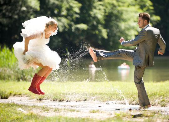 braut und bräutigam in fluss beim nass spritzen und spaß haben