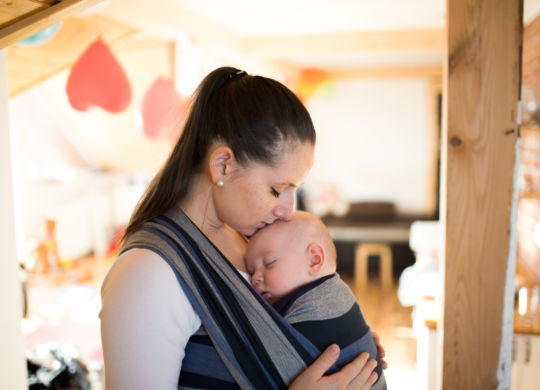 Beautiful young mother at home with her baby son sleeping in sling, kissing him on head