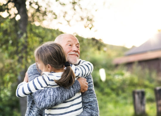 Grandfather giving his grandaughter a hug. Senior man and a small girl enjoying time in nature.