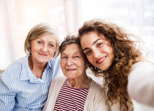 A teenage girl with her mother and grandmother at home. Family and generations concept.