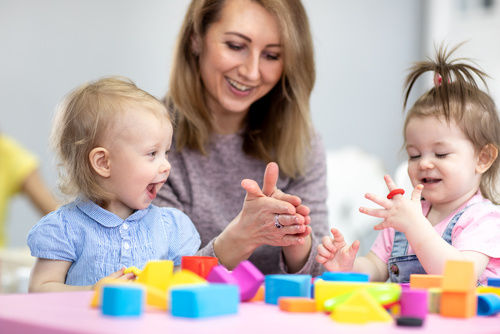 Woman teaches children modeling plasticine in day care center