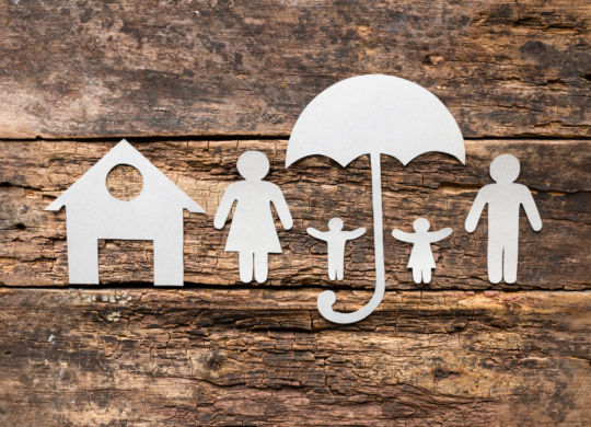 silhouettes of a family of paper under umbrellas near the house - the concept of protection and insurance