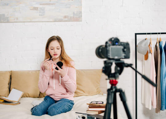 Teenage blogger sitting on bed and doing makeup in front of video camera
