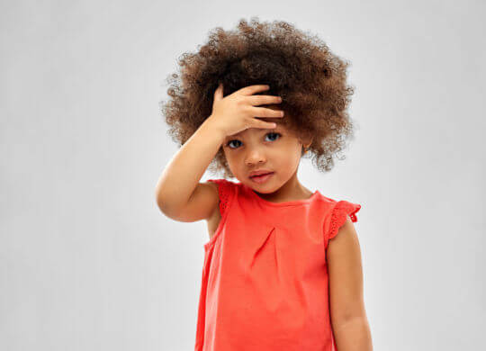 childhood and people concept - sad little african american girl touching her forehead over grey background