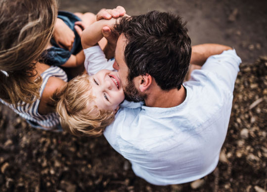 A top view of young family with two toddler children spending time outdoors by the river in summer, having fun.